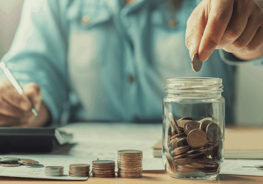 hand putting coins in jar