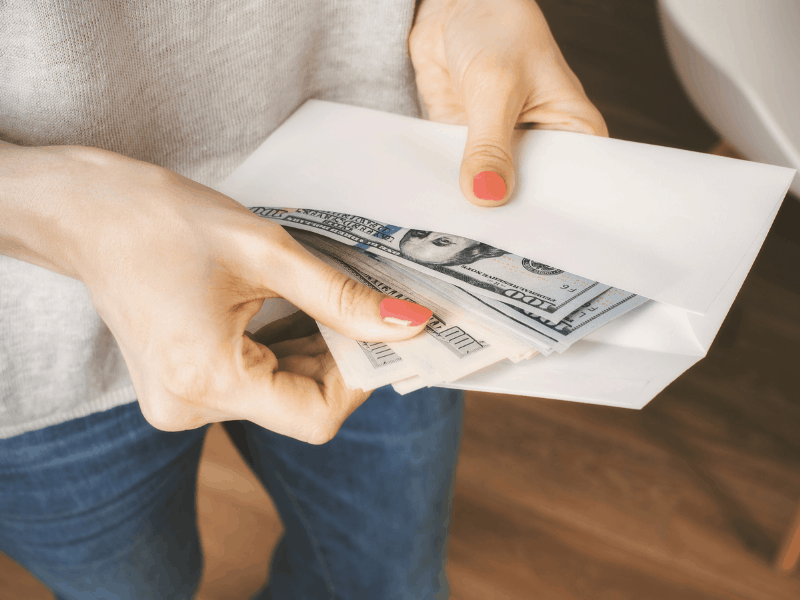 woman taking cash out of an envelope