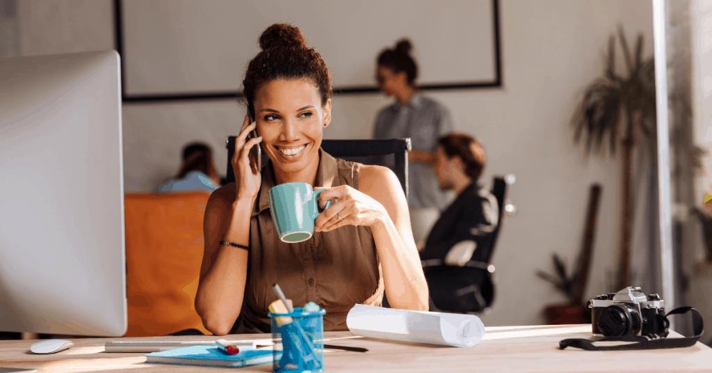 woman working at computer holding mug